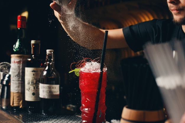 Barmannen handen sprenkelen het sap in het cocktailglas gevuld met alcoholische drank Premium Foto