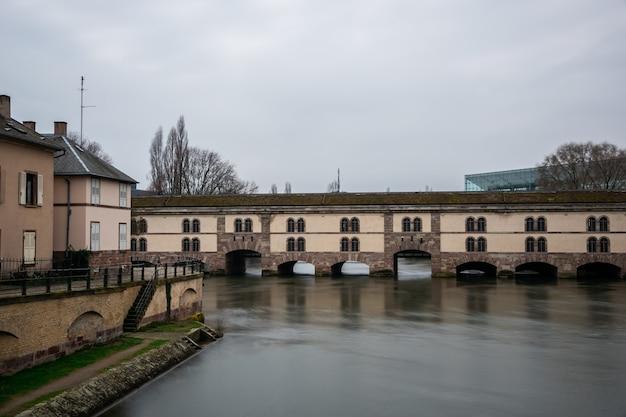 Barrage vauban omgeven door water en gebouwen onder een bewolkte hemel in straatsburg in frankrijk Gratis Foto