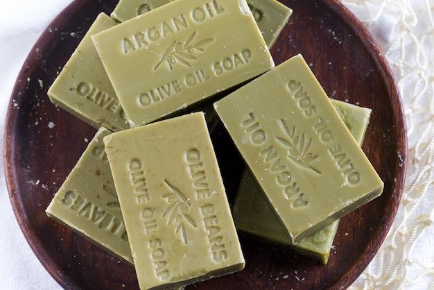 Bars van groene natuurlijke olijfoliezepen op een houten plaat Premium Foto