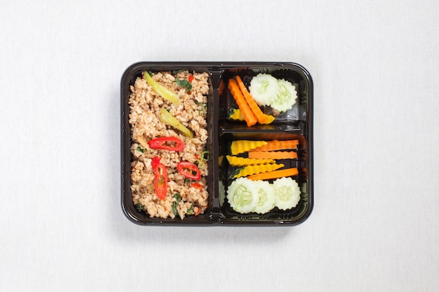 Basilicum gebakken rijst met varkensgehakt, in een zwarte plastic doos gedaan, op een wit tafelkleed, voedseldoos, pittig gebakken varkensvlees met basilicumbladeren, thais eten. Premium Foto
