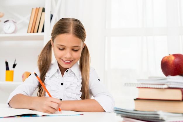 Basisschoolmeisje die thuiswerk doen Gratis Foto