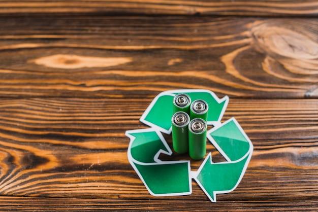 Batterij in het recycle pictogram op houten gestructureerde achtergrond Gratis Foto