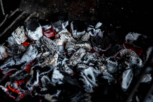 Bbq grill pit met gloeiende en vlammende hete houtskoolbriketten, voedselmuur of textuur, brandend brandhout in de open haard close-up, bbq vuur, houtskoolmuur. houtskoolvuur met vonken. brand Premium Foto