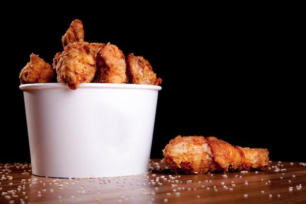 Bbq-kippenbenen in een witte emmer op een houten tafel Premium Foto