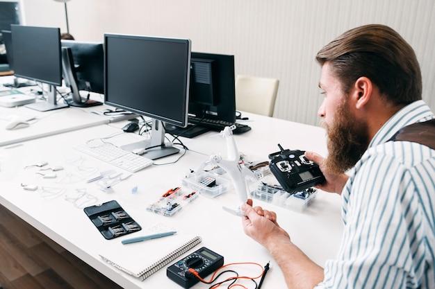 Beambte montage drone op het werk. bebaarde man zit in open ruimte met quadrocopter en gereedschap, en construeert elektronisch speelgoed Premium Foto