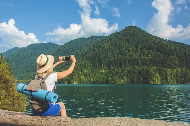 Beautiful girl traveller maakt foto's van een groot blauw bergmeer op de achtergrond van de bergen Premium Foto