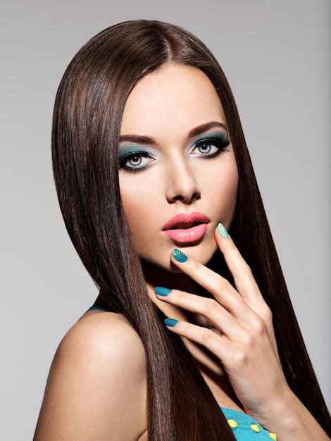 Beautiul elegante vrouw met turquoise make-up en nagels - pose Gratis Foto