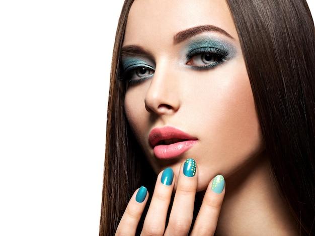 Beautiul mode vrouw met turquoise make-up en nagels - op witte muur Gratis Foto