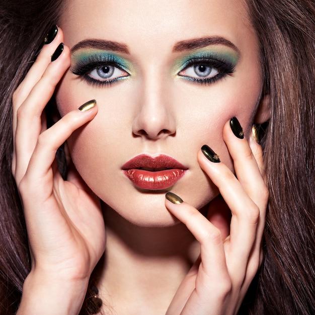 Beautiulvrouw met groene samenstelling en creatieve kleur van spijkers Gratis Foto