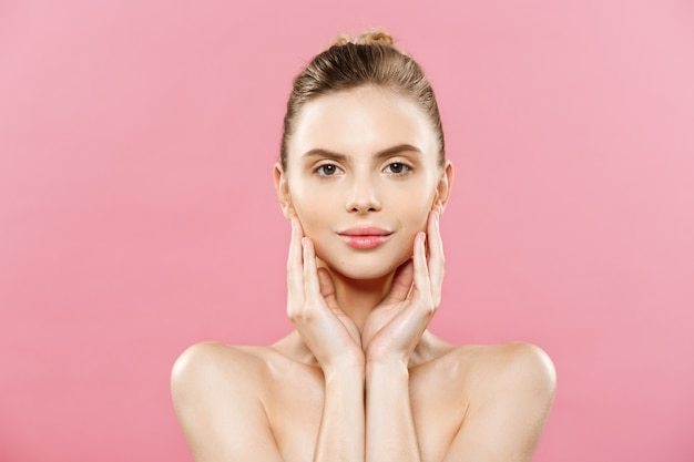 Beauty concept - mooie blanke vrouw met schone huid, natuurlijke make-up geïsoleerd op fel roze achtergrond met kopie ruimte. Gratis Foto