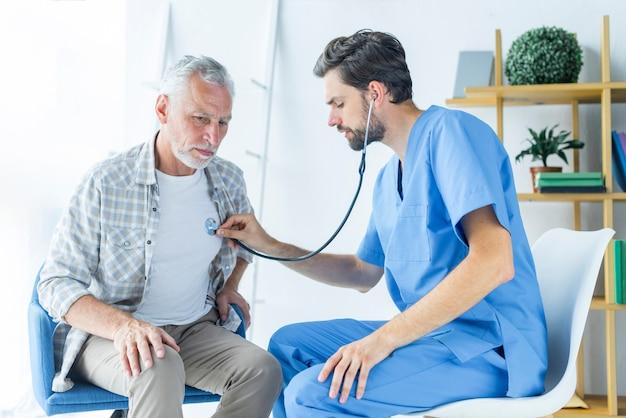 Bebaarde arts die longen van patiënt onderzoekt Gratis Foto