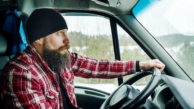 Bebaarde bead driver rijdt in het bos Premium Foto