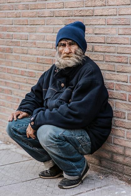 Bebaarde dakloze man voor bakstenen muur Gratis Foto