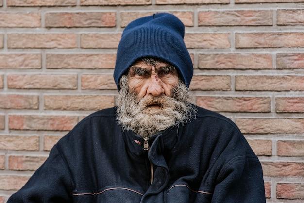 Bebaarde dakloze man voor muur Gratis Foto