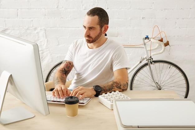 Bebaarde getatoeëerde freelancer in lege witte t-shirt werkt op zijn computer thuis voor bakstenen muur en geparkeerde vintage fiets, zomertijd Gratis Foto
