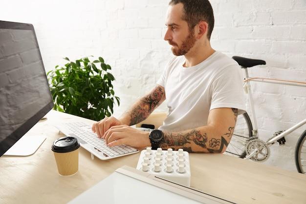 Bebaarde getatoeëerde man in lege witte t-shirt werkt op zijn computer thuis, zijaanzicht, zomertijd Gratis Foto