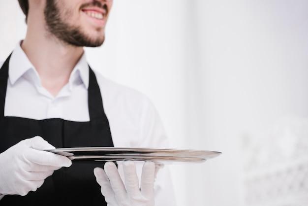 Bebaarde kelner met metalen dienblad Gratis Foto