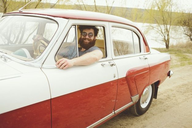 Bebaarde man achter het stuur van een retro auto Premium Foto