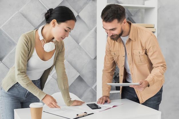 Bebaarde man en aziatische vrouw die op het klembord kijken Gratis Foto
