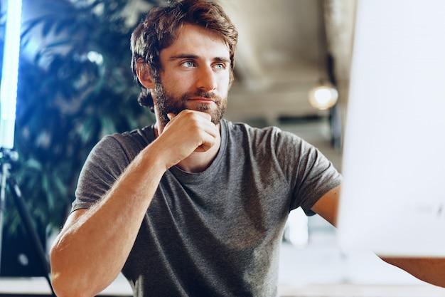 Bebaarde man freelancer met behulp van computer in een moderne naaiatelier. freelance bedrijfsconcept Premium Foto