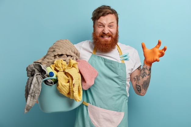 Bebaarde man houdt wasmand vast, overweldigd door huishoudelijke taken Gratis Foto