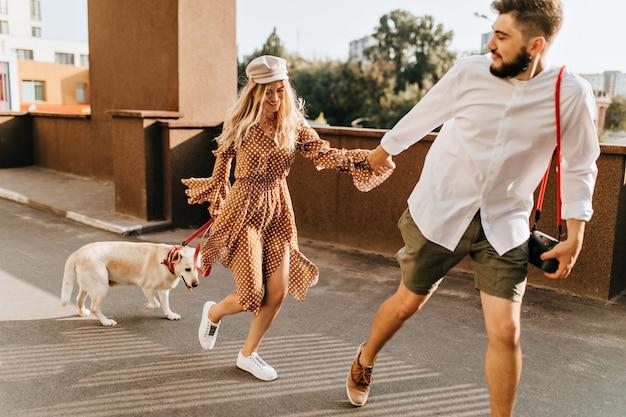 Bebaarde man in kaki korte broek houdt blond meisje met de hand vast en rent. paar genieten van zomerwandeling met hond. Gratis Foto