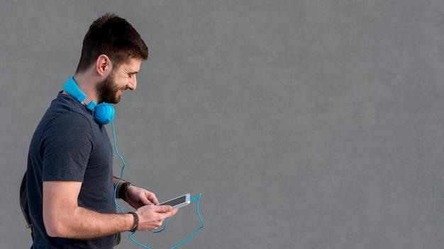 Bebaarde man met een koptelefoon op de nek met behulp van de tablet Gratis Foto