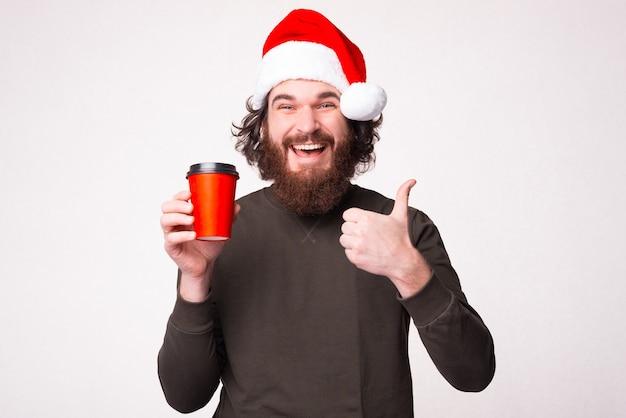 Bebaarde man met kopje koffie te gaan en duim opdagen en het dragen van kerstman hoed Premium Foto