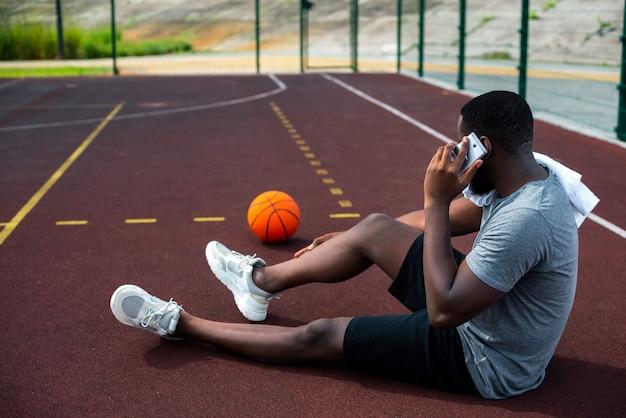 Bebaarde man praten over de telefoon lang schot Gratis Foto