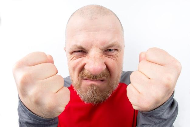 Bebaarde man van dreigende blik met gebalde vuisten close-up op wit Premium Foto