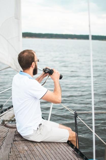 Bebaarde man verrekijker kijken op de zeilboot Premium Foto