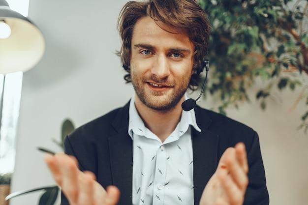 Bebaarde man zakenman met hoofdtelefoon met online zakelijk gesprek Premium Foto