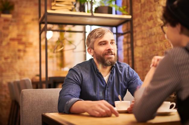 Bebaarde mens in vrijetijdskleding die bij lijst in koffie zitten, thee hebben en op datum met zijn vriendin in wisselwerking staan Premium Foto
