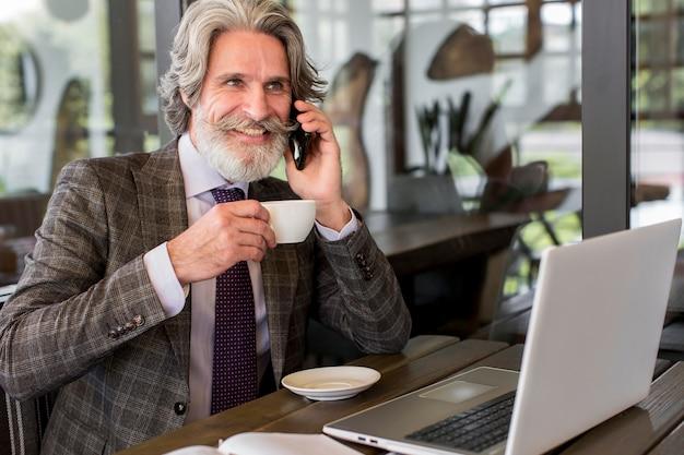 Bebaarde volwassen man genieten van koffie op kantoor Gratis Foto