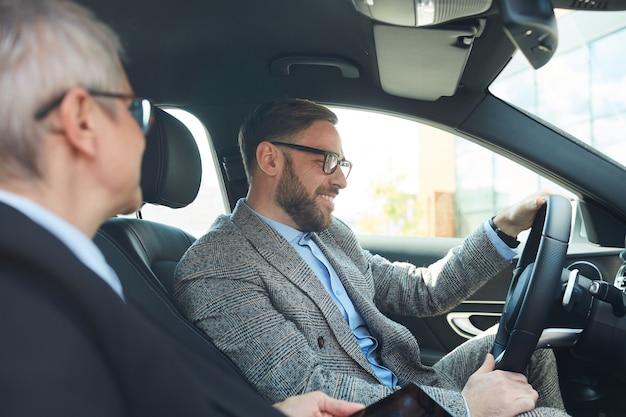 Bebaarde volwassen zakenman in brillen auto rijden en praten met volwassen zakenvrouw Premium Foto