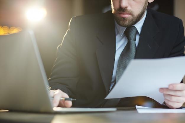 Bebaarde zakenman die met documenten in bureau werkt Gratis Foto