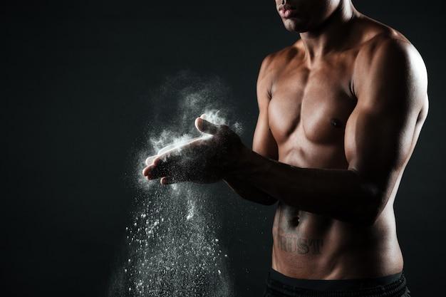 Bebouwd beeld van de knappe mens die van afro amerikaanse sporten handen met krijt wrijven Gratis Foto
