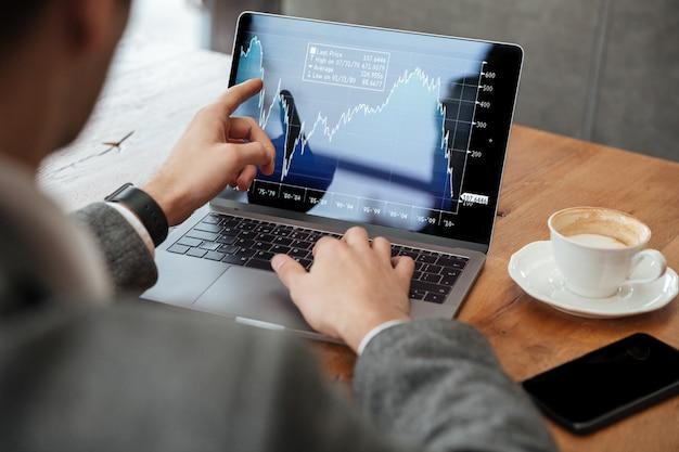 Bebouwd beeld van zakenmanzitting door de lijst in koffie en het analyseren van indicatoren op laptop computer Gratis Foto