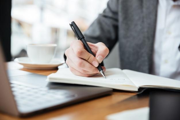 Bebouwd beeld van zakenmanzitting door de lijst in koffie met laptop computer en het schrijven van iets Gratis Foto