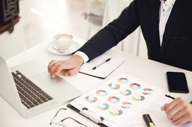 Bebouwd frontview van een zakenman werkende plaats in het restaurant met laptop, mobiel, diagrammen en latte Gratis Foto