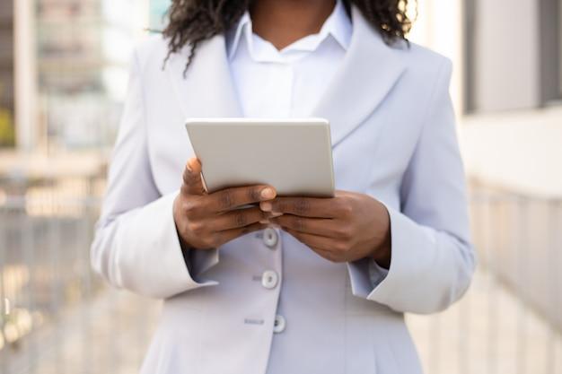 Bebouwd schot van afrikaanse amerikaanse onderneemster die tablet gebruiken. vrouwelijke handen die modern digitaal apparaat houden. technologie concept Gratis Foto