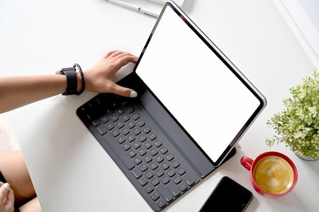 Bebouwd schot van creatieve ontwerper die met modern tablet en toetsenbord aan witte lijst bij studiowerkruimte werken Premium Foto