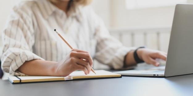 Bebouwd schot van jonge professionele onderneemster die aan haar project werkt en op notitieboekje schrijft Premium Foto