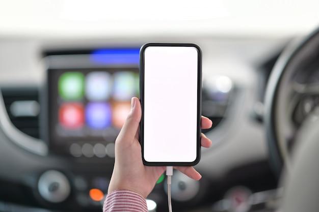 Bebouwd schot van vrouwelijke hand die mobiele telefoon in auto houdt. Premium Foto