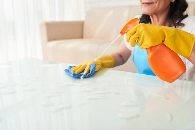 Bebouwd vrouwen bespuitend detergens op de koffietafel Gratis Foto