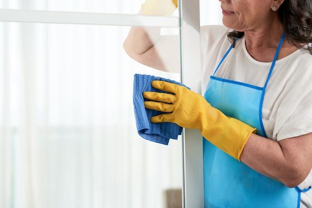 Bebouwd vrouwen schoonmakend venster die speciale schort dragen Gratis Foto