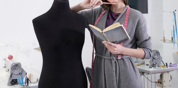 Bebouwde mening van naaister die zwart model in workshop meten, het werk van de kleermakersstudio Premium Foto