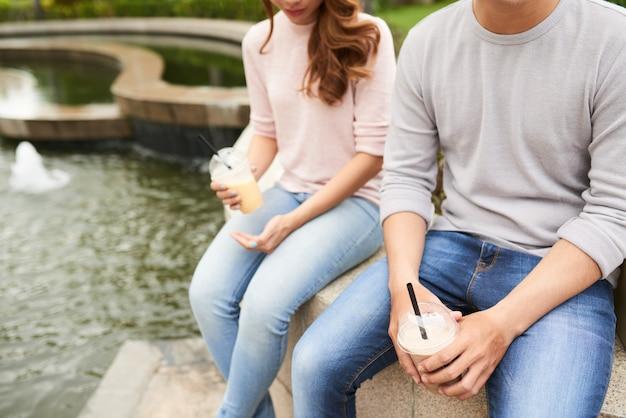 Bebouwde mening van onherkenbaar paar die van cocktails in het park genieten Gratis Foto