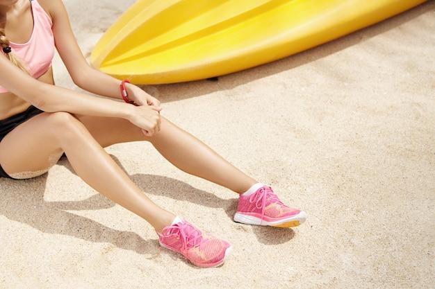 Bebouwde mening van vrouwelijke agent die roze loopschoenen dragen die rust op zand in openlucht hebben na actieve lichaamsbeweging. jonge sportvrouw in sportkleding ontspannen op het strand tijdens de ochtend training Gratis Foto
