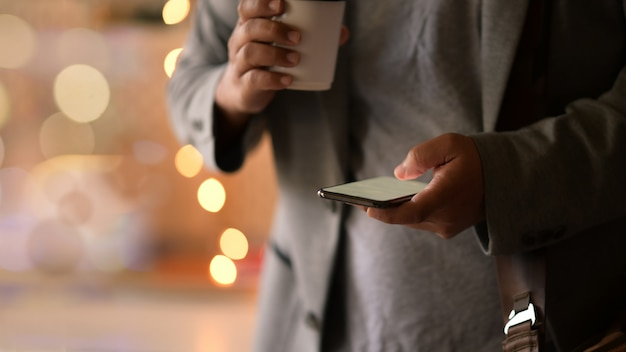 Bebouwde shot man met behulp van mobiele telefoon op straat lopen nacht. Premium Foto